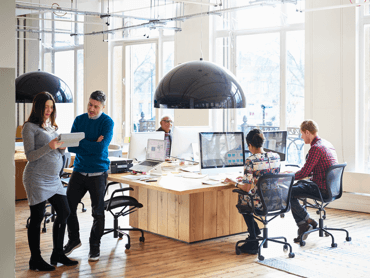 Colleagues work and talk around a central desk in an airy, open-concept office.